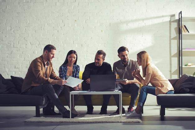 Geschäftsleute, die im internet mit einem laptop in einem ruheraumkonzept des startup-unternehmens verbunden sind