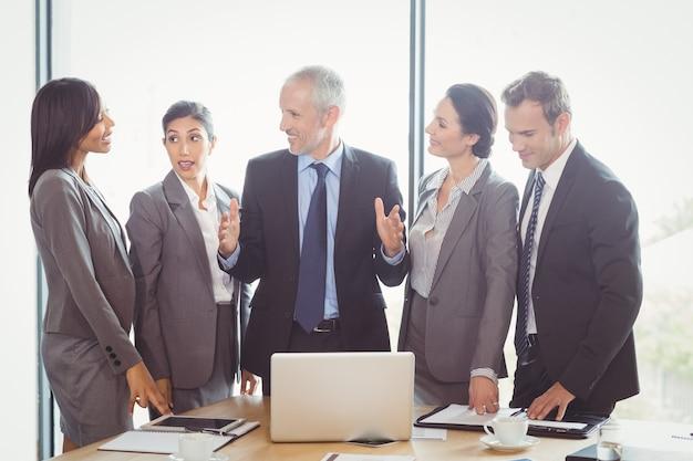 Geschäftsleute, die im konferenzraum aufeinander einwirken
