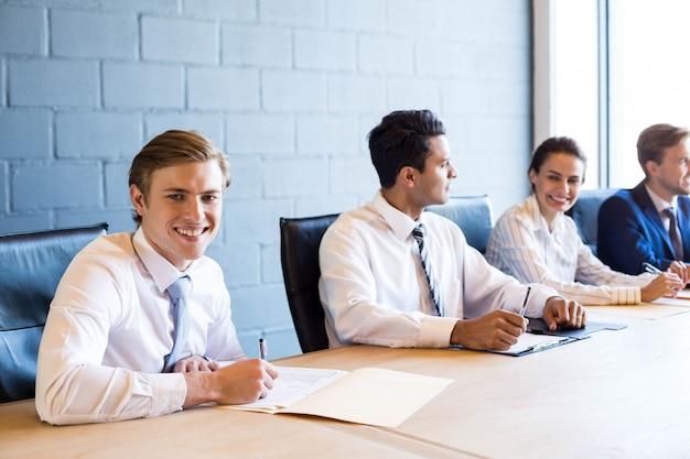 Geschäftsleute, die in der sitzung am konferenztisch im büro sich besprechen