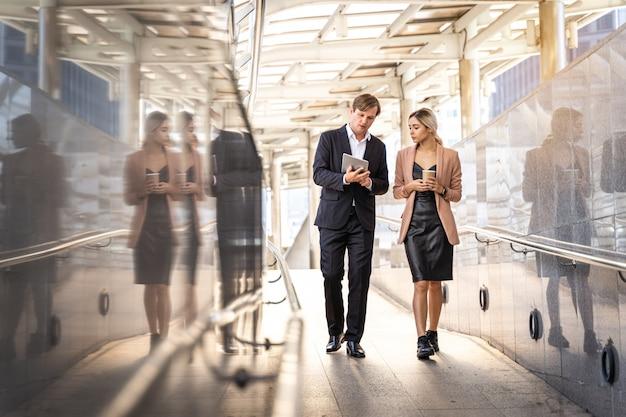 Geschäftsleute, die in die straße, glückliches teamwork-genießen gehen und sprechen
