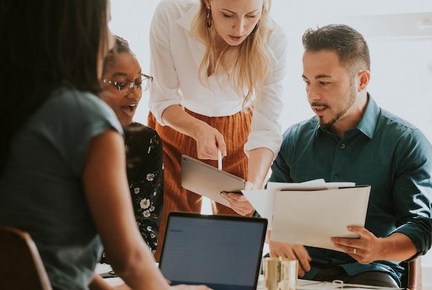 Geschäftsleute, die in einem meeting mit einem digitalen tablet arbeiten