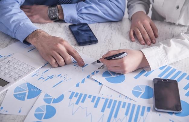 Geschäftsleute, die in finanzgraphen arbeiten. im büro arbeiten