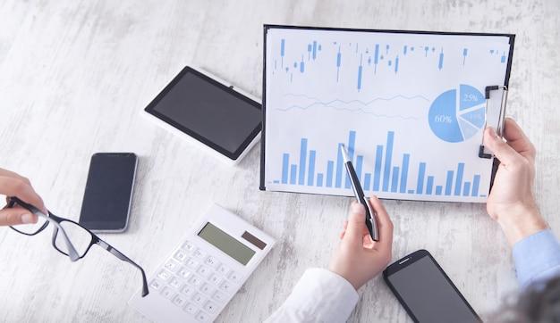 Geschäftsleute, die in finanzgraphen arbeiten. investition