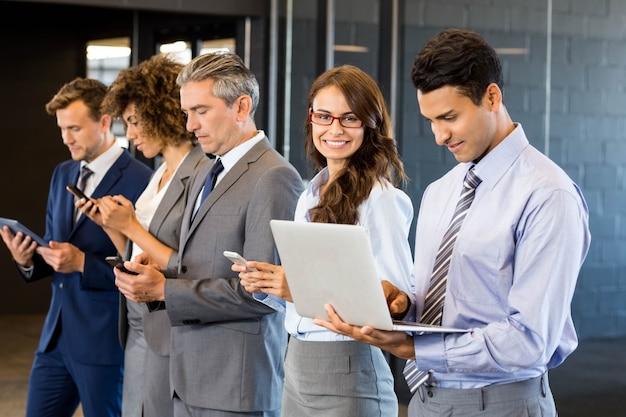 Geschäftsleute, die in folge stehen und handy, laptop und digitale tablette im büro verwenden