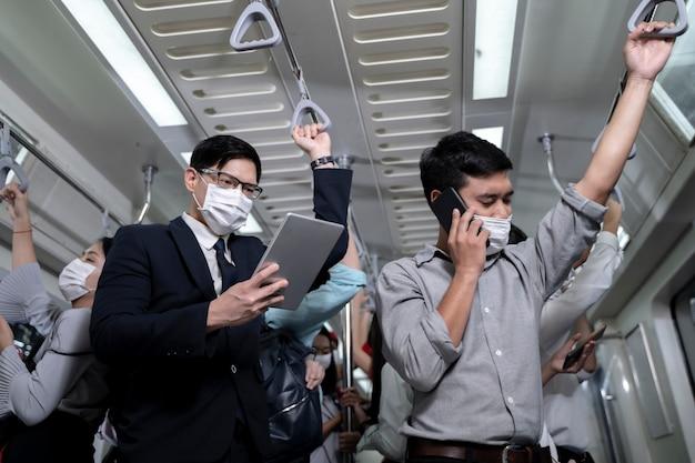 Geschäftsleute, die in u-bahn-u-bahn stehen. mann mit tablette und smartphone. menschen mit gesichtsmaske. coronavirus-grippevirus im öffentlichen verkehr.
