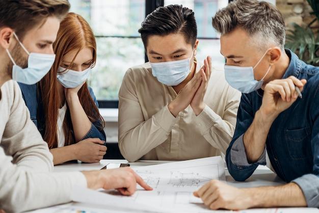Geschäftsleute, die medizinische masken bei der arbeit tragen
