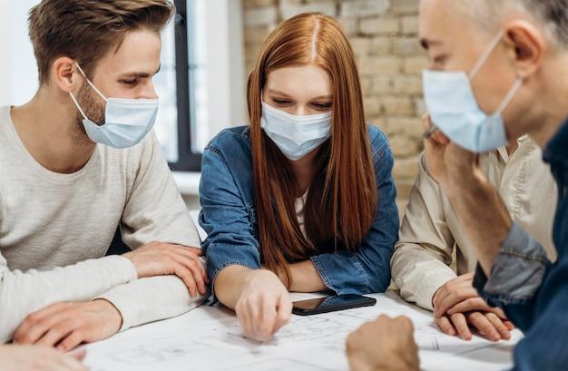 Geschäftsleute, die medizinische masken im büro tragen