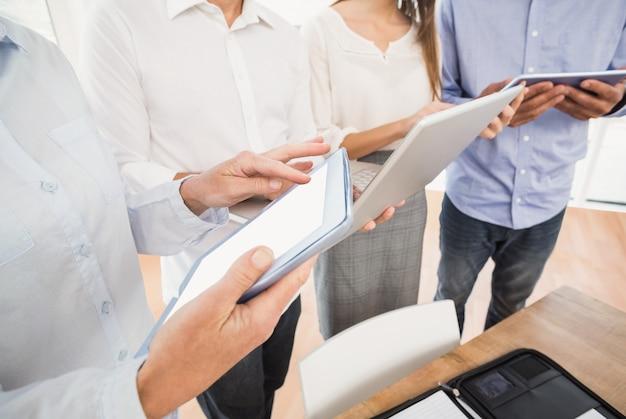 Geschäftsleute, die mehrere elektronische geräte verwenden