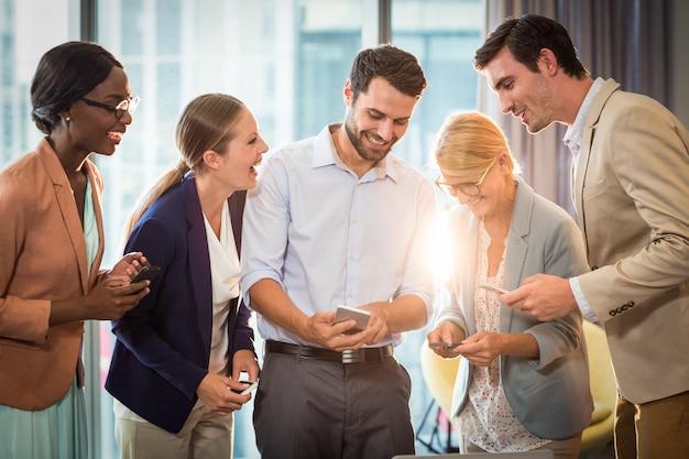 Geschäftsleute, die mit dem mobiltelefon interagieren