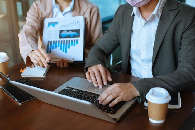 Geschäftsleute, die mit finanzdokumentdatendiagrammen und -diagrammen diskutieren team-geschäftstreffen mit smartphone und laptop und digitalem tablet-computer