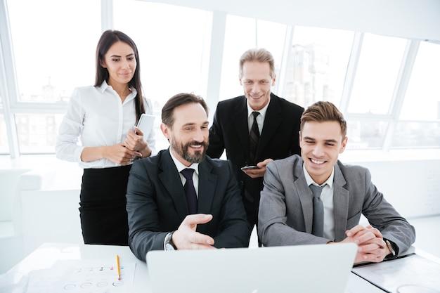 Geschäftsleute, die mit laptop im büro am tisch sitzen