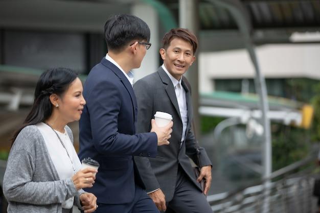 Geschäftsleute, die morgens zur arbeit gehen, übergeben das halten der kaffeetasse