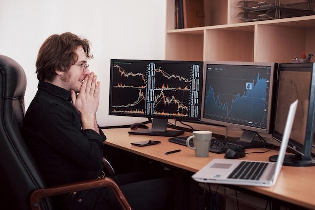 Geschäftsleute, die online mit aktien handeln. börsenmakler, der diagramme, indizes und zahlen auf mehreren bildschirmen betrachtet. geschäftserfolg konzept