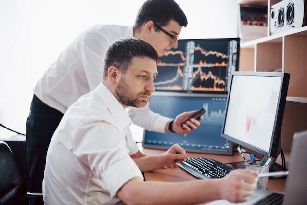 Geschäftsleute, die online mit aktien handeln. börsenmakler, die diagramme, indizes und zahlen auf mehreren bildschirmen betrachten. kolleginnen und kollegen diskutieren im händlerbüro. geschäftlicher erfolg
