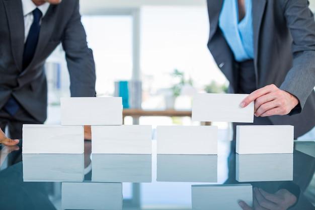 Geschäftsleute, die papierblock stapeln