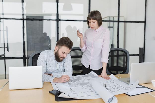 Geschäftsleute, die pläne im büro betrachten