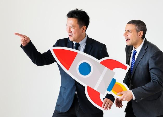 Geschäftsleute, die raketenikone halten