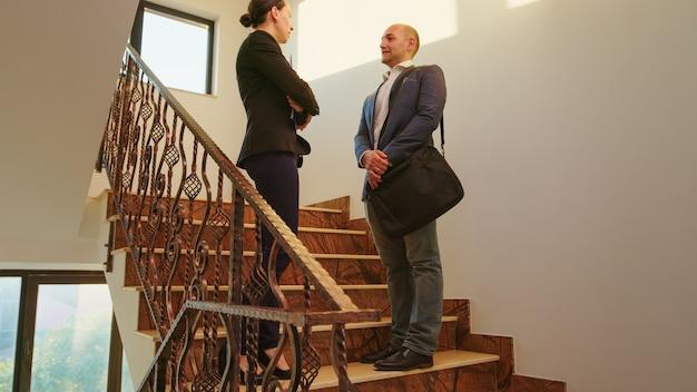 Geschäftsleute, die sich auf treppen in der finanzgesellschaft treffen, die hände schütteln und reden. team von professionellen geschäftsleuten, die im modernen finanzgebäudegruß zusammenarbeiten.