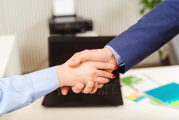 Geschäftsleute, die sich im büro die hände schütteln. abschluss eines erfolgreichen meetings. händedrucknahaufnahme der geschäftsfrau und des geschäftsmannes. handshake-geschäftspartner.