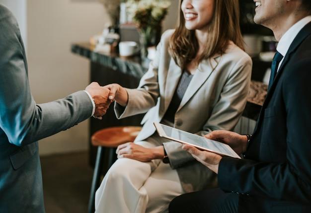 Geschäftsleute, die sich in einem café die hand schütteln