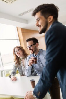 Geschäftsleute, die spaß haben und im büro am arbeitsplatz chatten