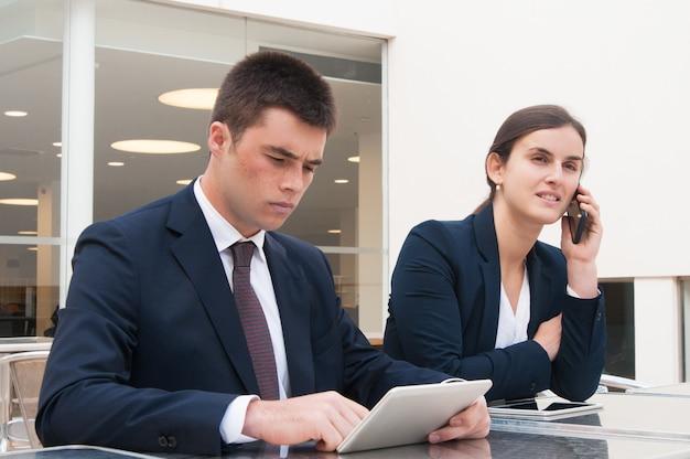 Geschäftsleute, die tablette verwenden und um telefon am schreibtisch ersuchen