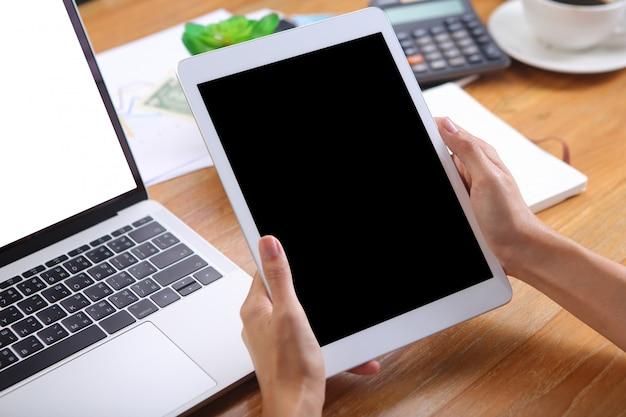 Geschäftsleute, die tablettenmodell mit hölzernem schreibtisch des laptopmodells und des bürobriefpapiers halten