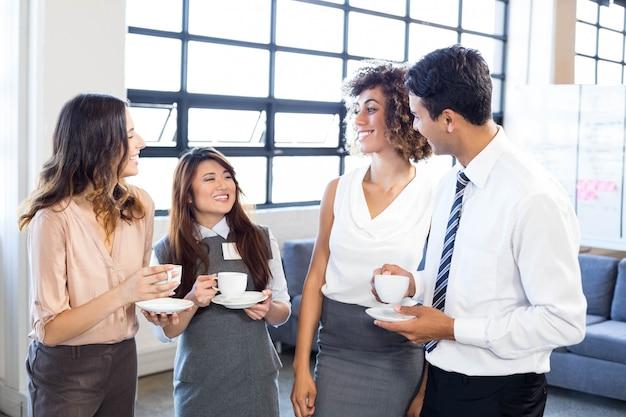 Geschäftsleute, die tee trinken und während der pausen im büro aufeinander einwirken