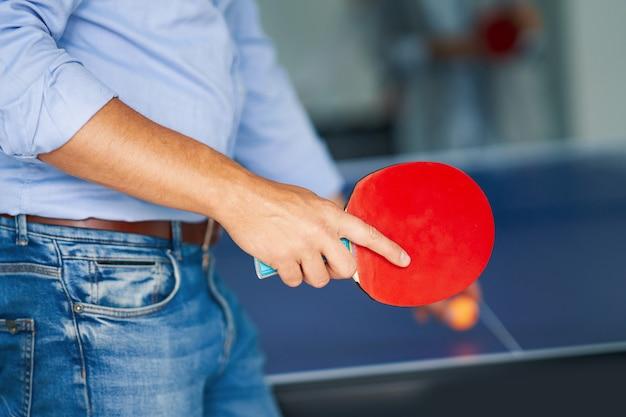 Geschäftsleute, die tischtennis in gemeinsamen büroräumen spielen