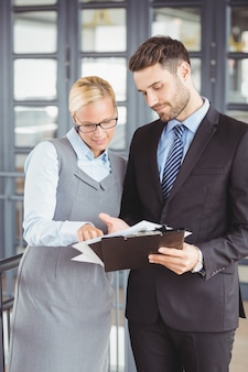 Geschäftsleute, die über dokumenten im büro sich besprechen