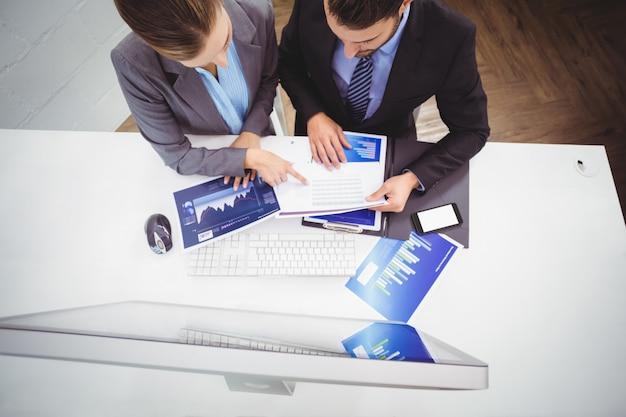 Geschäftsleute, die über dokumenten sich besprechen