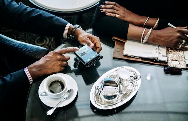 Geschäftsleute, die über ein abkommen im café sich besprechen