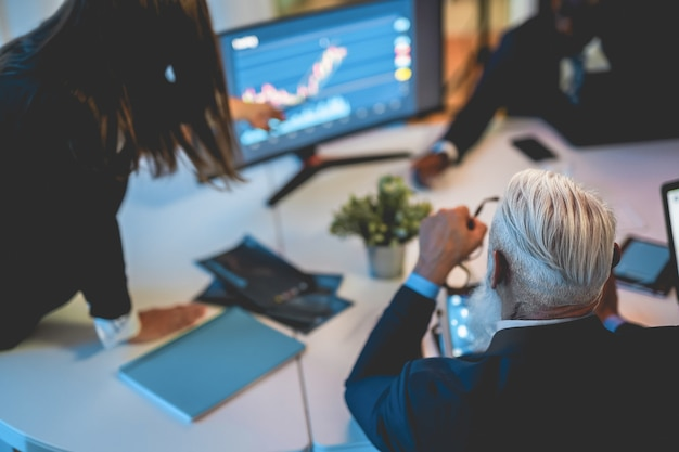 Geschäftsleute, die über neue handelsstrategien im bankkonferenzraum sprechen - konzentrieren sie sich auf den kopf des leitenden mannes