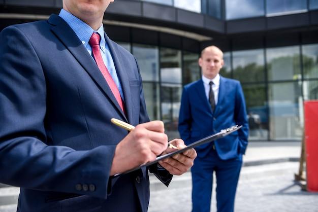 Geschäftsleute, die vertrag nahe wolkenkratzer im freien unterzeichnen