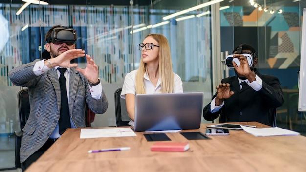 Geschäftsleute, die während des meetings eine virtual-reality-brille verwenden. entwicklerteam testet das virtual-reality-headset und diskutiert neue ideen, um das visuelle erlebnis zu verbessern.