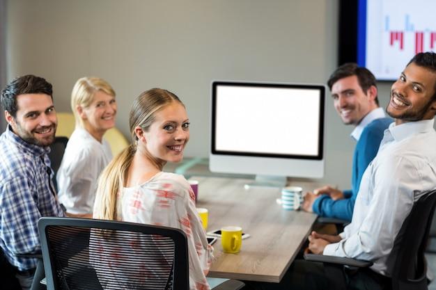 Geschäftsleute, die während einer videokonferenz in die kamera lächeln