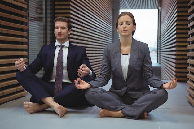 Geschäftsleute, die yoga im korridor ausführen