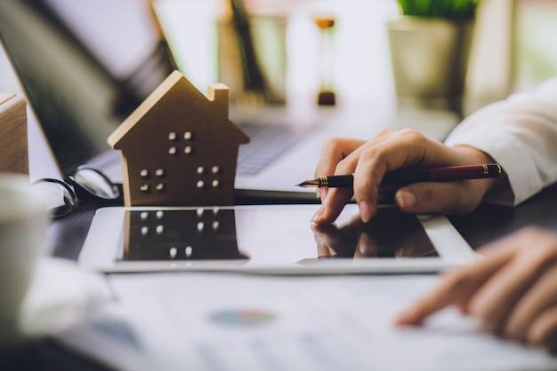 Geschäftsleute, die zinsen, steuern und gewinne berechnen, um in immobilien und haus zu investieren