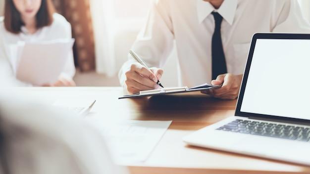 Geschäftsleute, die zusammen an laptop beim treffen von designideen arbeiten. weinleseton.