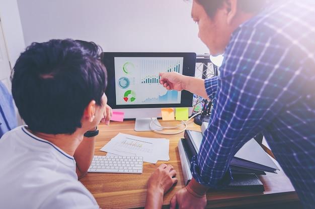 Geschäftsleute, die zusammen daten in teamwork für die planung und inbetriebnahme eines neuen projekts analysieren