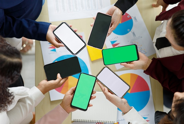 Geschäftsleute, die zusammen im büro über dem schreibtisch mit buntem diagramm und diagrammen sitzen, halten smartphones in verschiedenen modellen mit leeren bildschirmen. aufgenommen aus dem blickwinkel von oben.