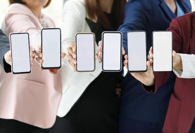 Geschäftsleute, die zusammen im büro über dem schreibtisch mit buntem diagramm und diagrammen sitzen, halten smartphones in verschiedenen modellen mit leeren bildschirmen.