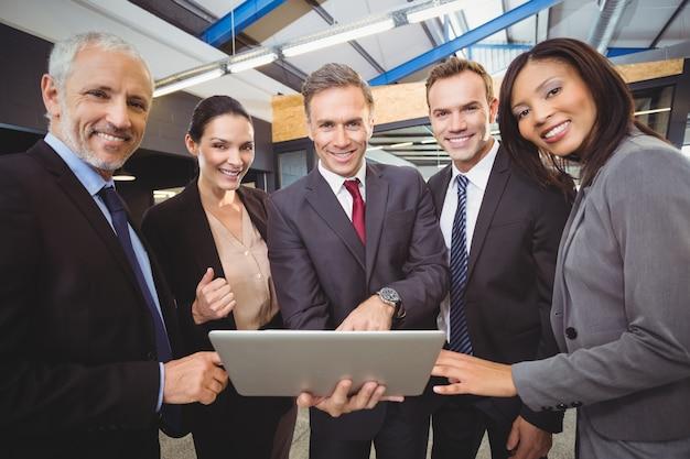 Geschäftsleute, die zusammen mit einem laptop stehen