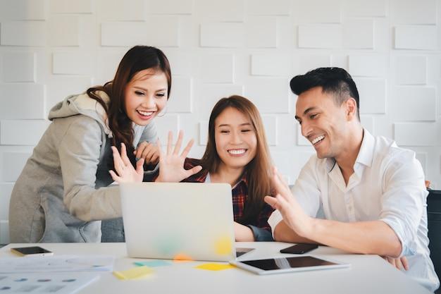 Geschäftsleute, die zusammen mit glücklichem gefühl an der webcamkamera auf laptop-computer arbeiten