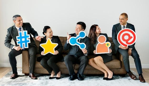 Geschäftsleute, die zusammen mit ikonen sitzen
