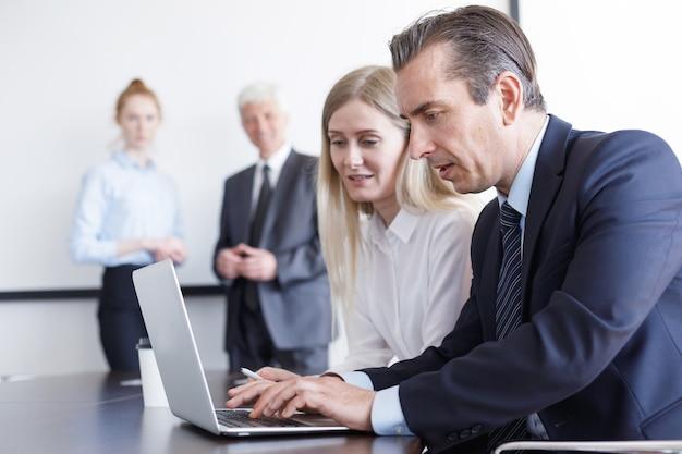 Geschäftsleute, die zusammen mit laptop im büro arbeiten