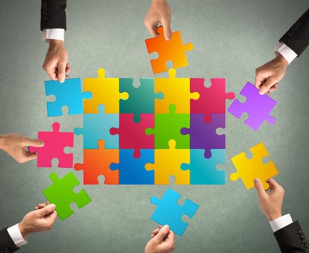Geschäftsleute, die zusammenarbeiten, um ein farbiges puzzle zu bauen