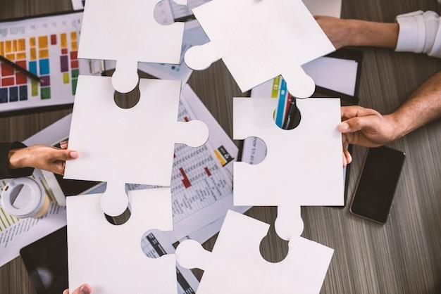 Geschäftsleute, die zusammenarbeiten, um ein puzzle zu bauen. konzept von teamwork, partnerschaft, integration und startup.