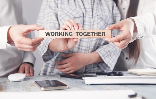 Geschäftsleute, die zusammenarbeitenden text auf holzblock zeigen.