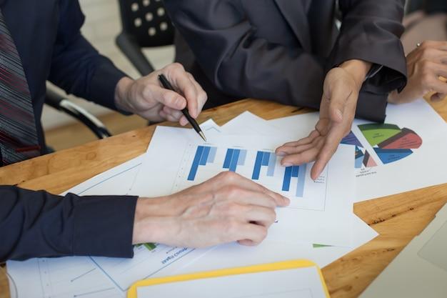 Geschäftsleute diskutieren die charts und grafiken, die die ergebnisse ihrer erfolgreichen teamarbeit zeigen.